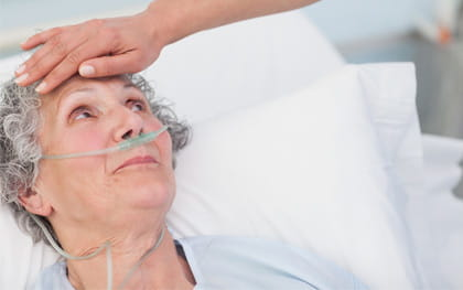 Elderly woman laying in bed receiving 24hr care