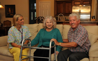 Caregiver sitting on couch with elderly couple
